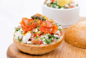 Bun with cottage cheese, tomato and salmon on a wooden board — Stock Photo
