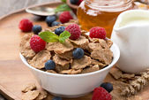 Cereal flakes with fresh berries, honey and milk for breakfast — Stock Photo