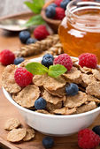 Cereal flakes with berries, honey and milk for breakfast — Stock Photo