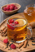 Fragrant black tea with lemon, raspberry and cinnamon — Stock Photo