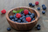 Fresh blueberries and raspberries in wooden bowl — Stock Photo