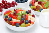 Fruit and berry salad and jug of cream — Stock Photo