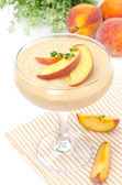 Peach souffle in glass and fruit in the background, close-up — Stock Photo