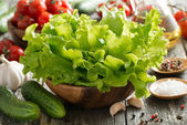 Bowl with fresh salad, vegetables, spices and olive oil — Stock Photo