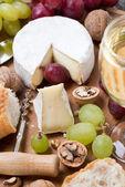 Camembert, copo de vinho branco, uvas e baguetes frescas — Fotografia Stock