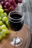 Glass of red wine and grapes on a wooden board — Stock Photo