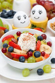 Fruit salad with whipped cream and painted eggs for breakfast — Stock Photo