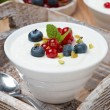 Natural yogurt with fresh berries in a bowl on wooden tray — Stock Photo #45826761