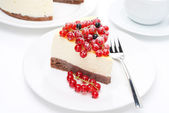 Piece of cheesecake with red and black currants and coffee — Stock Photo