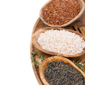 Three kinds of rice and thyme in a wooden bowl, top view — Stock Photo