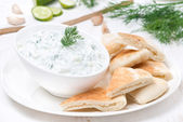 Yoghurt sauce tzatziki with pieces of pita bread — Stock Photo