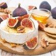 Fresh camembert cheese with honey, figs and crackers — Stock Photo #46216077