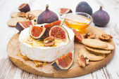 Fresh camembert cheese with honey, figs and crackers — Stock Photo
