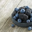 Bowl of fresh blackberries and blueberries on wooden background — Stockfoto #46593937