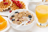 Muesli with milk, sweet waffles and orange juice for breakfast — Stock Photo