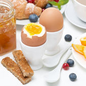 Breakfast with eggs, toasts, croissants, fresh berries — Stock Photo