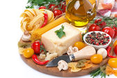 Parmesan, spices, tomatoes, olive oil, pasta and herbs on board — Stock Photo