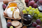 Assorted appetizers to wine - cheeses, fresh grapes, crackers — Stock Photo