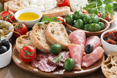 Assorted Italian antipasti - deli meats, fresh cheese, olives — Stock Photo