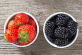 Strawberries and blackberries in bowls, top view — Stock Photo