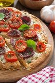 Heerlijke pizza met salami en tomaten op een houten bord — Stockfoto