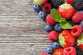 Wooden background with fresh berries and mint — Stock Photo