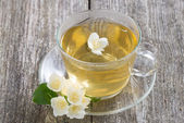 Cup of green tea with jasmine on wooden table, close-up — Foto de Stock