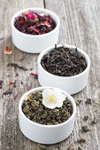Assorted dry herbal teas in white bowls, vertical — Stock Photo