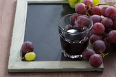 Blackboard for writing, glass of red wine and grapes — Stock Photo