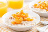 Bowl of oatmeal with fresh apricots and orange juice — Stock Photo