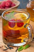 Black tea with lemon, mint, raspberry and cinnamon, close-up — Stock Photo