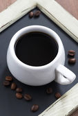 Cup of coffee on black chalkboard close-up, top view — Stock Photo