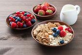Oatmeal and muesli in a bowl, fresh berries and milk — Stock Photo