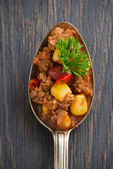Spicy Mexican dish chili con carne in a spoon, conceptual photo — Stock Photo