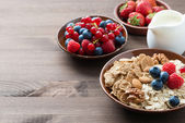 Oatmeal and muesli in a bowl, fresh berries and milk — Stock fotografie