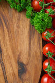 Wooden board background, fresh tomatoes and herbs, vertical — Stock fotografie