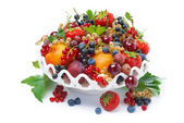 Dish with seasonal fruit and berries, isolated — Stock Photo