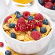 Cornflakes with berries in a bowl, milk and orange juice — Stock Photo #50276497