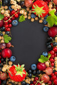 Black background for text with fresh garden berries, vertical — Stock Photo