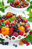 Dish with fresh seasonal fruit and berries on table, vertical — Stock Photo