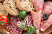 Assorted Italian antipasti - deli meats, olives and bread — Stock Photo