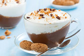 Dessert with chocolate, cream and amaretti on a blue background — Foto Stock