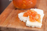 Sweet quince jam with almonds on white cheese — Stock Photo