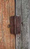 Old door hinge on wooden door — Stock Photo