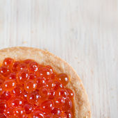 Tartlet with red caviar on light wooden background — Stock Photo