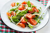 Fresh snow peas and tomato salad on plate — Stock Photo