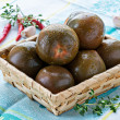 Kumato (brown) tomatoes in basket — Stock Photo