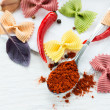 Dry multicolored farfalle pasta and smoked paprika — Stock Photo