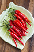 Red hot chili peppers on plate over wooden background — Stock Photo