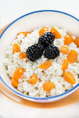Bowl of cottage cheese with berries on light background — Stock Photo